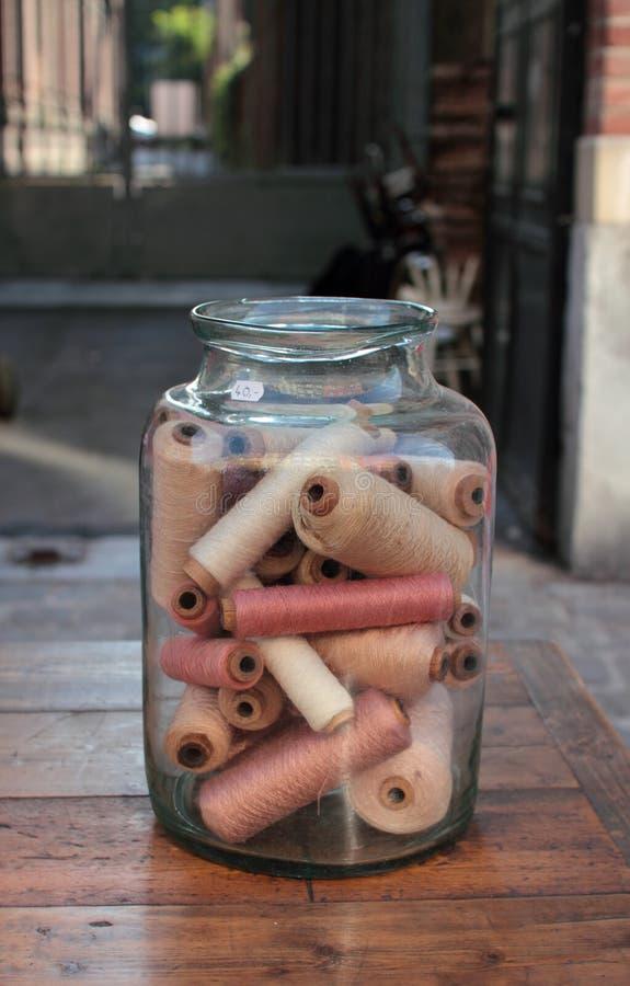 Old bobbins in glass jar royalty free stock image
