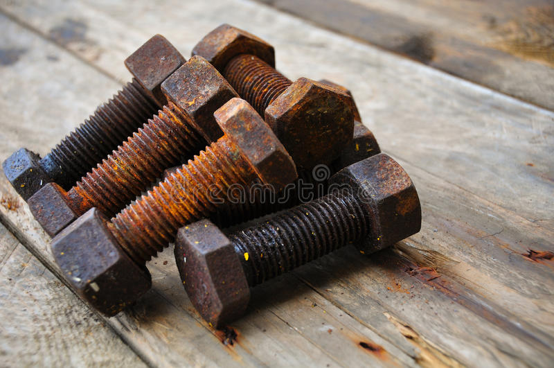 Old bolts or dirty bolts on wooden background, Machine equipment in industry work.  royalty free stock photography