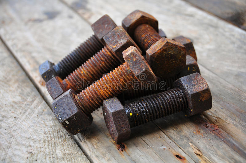 Old bolts or dirty bolts on wooden background, Machine equipment in industry work.  royalty free stock images
