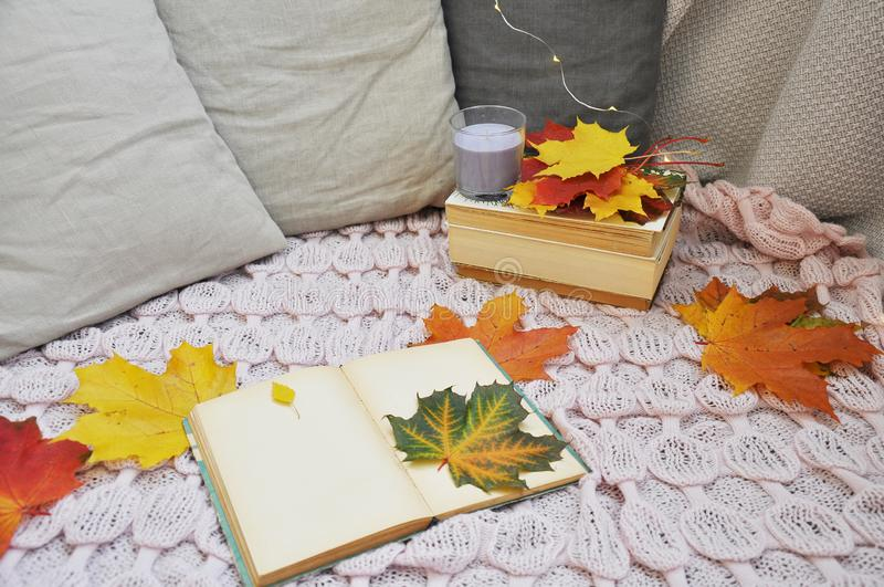 Old book with autumn leaves and candles stock photos