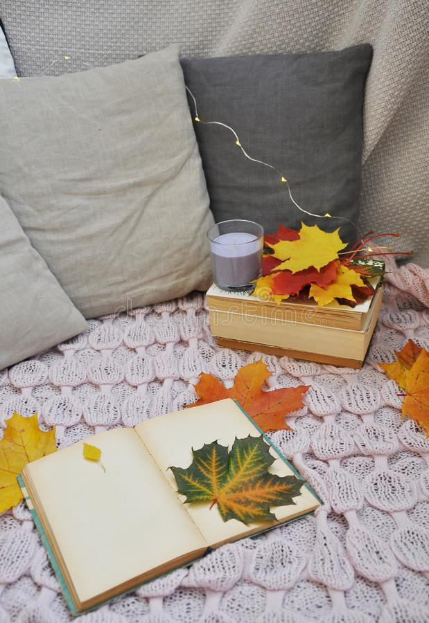 Old book with autumn leaves and candles stock photo