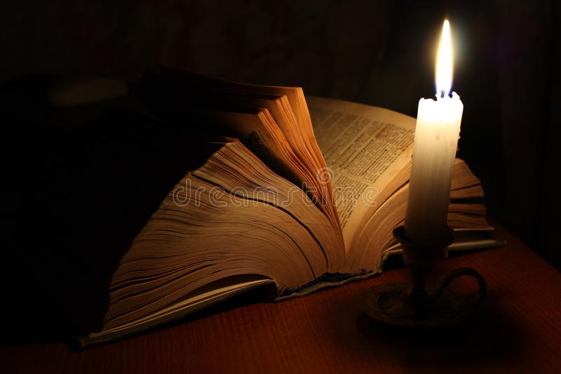 Old book and candle royalty free stock images