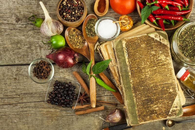 Old book of cookery recipes. Culinary background and recipe book with various spices on wooden table. stock image