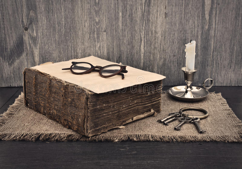 Old book, glasses and a bunch of keys. On wooden background stock images