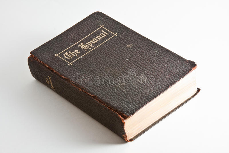 Old Book - The Hymnal. Isolated view of an old hymnal with worn and torn leather cover and gold lettering royalty free stock images
