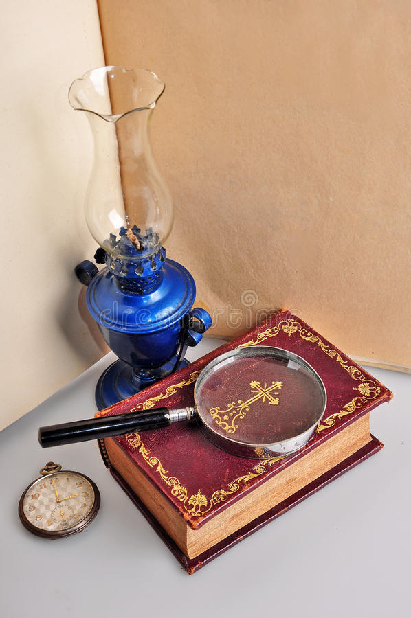 Old book lamp and watch. Old Bible book with magnifier ,lamp and pocket watch stock photos