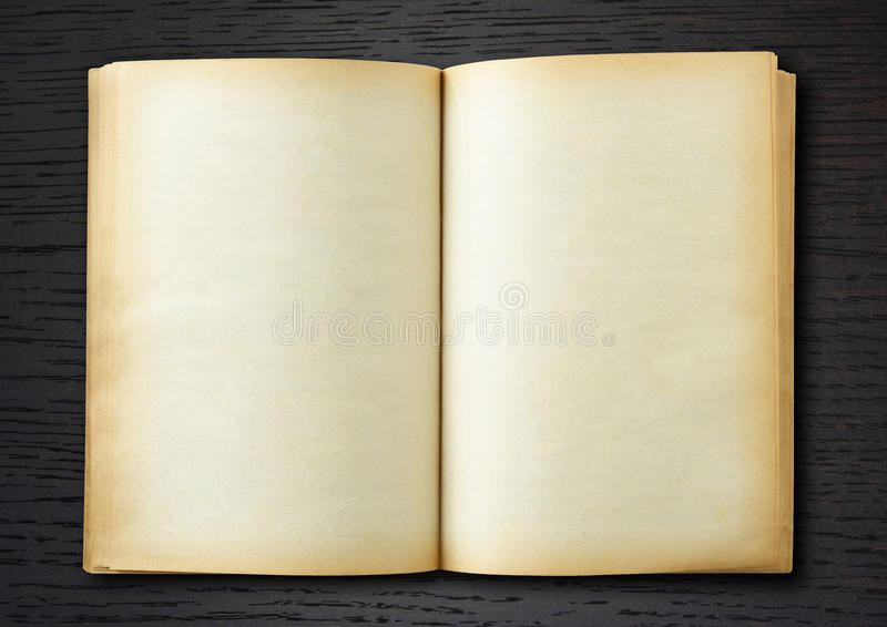 Old book open on dark wood background. Vintage book stock photo