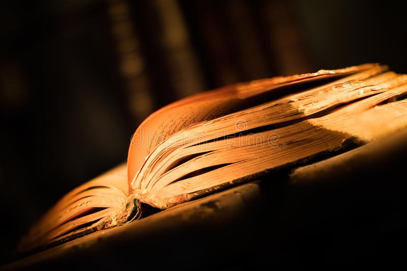 Old old book with open pages and quill pen on wooden table stock photo