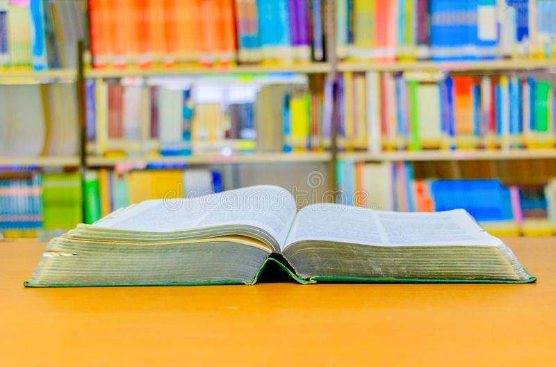 old book open in school library on wooden table. blurry bookshelves background stock images