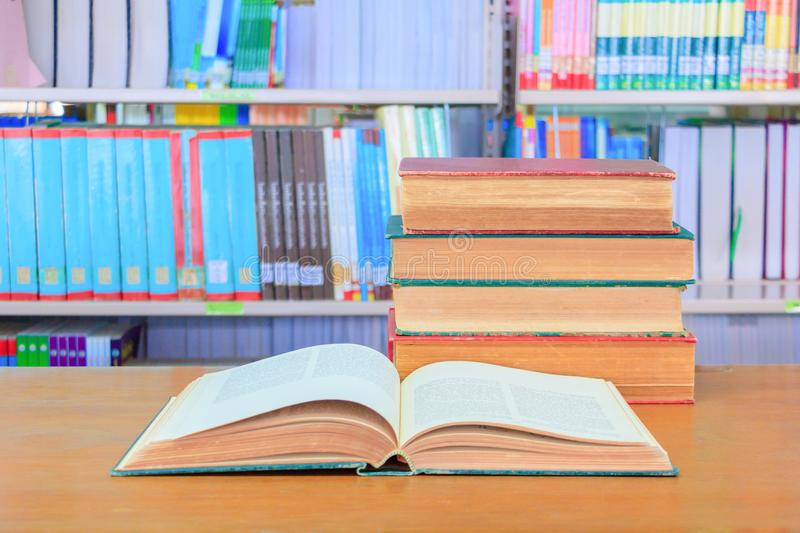 Old book open in school library on wooden table. blurry bookshelves background. Education learning concept with copy space add text royalty free stock photo