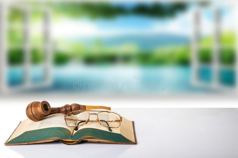 An old book with a pair of glasses and a tobacco pipe on them i. N front of bright blurred natural background. The teachers day. Back to school. Space royalty free stock images