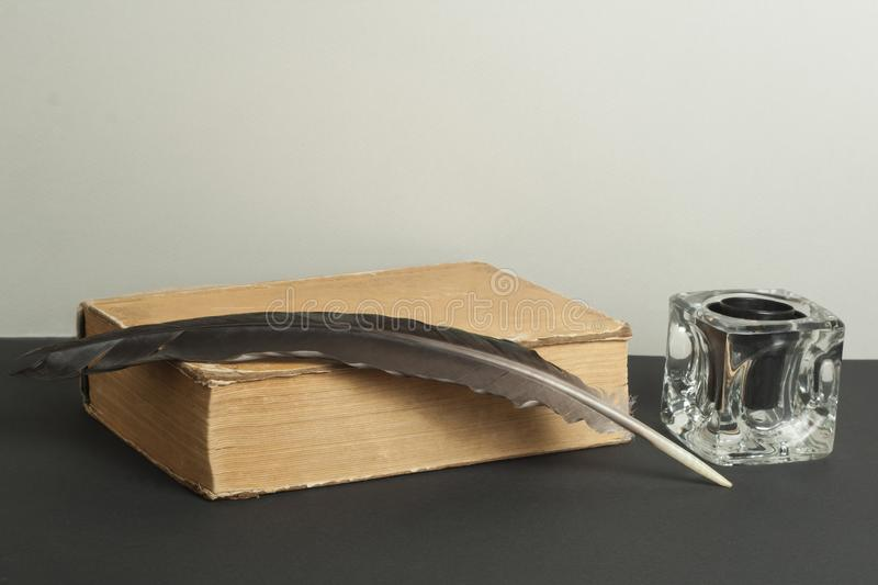 Old book and quill pen with inkwell on wooden table. Free copy space. stock image