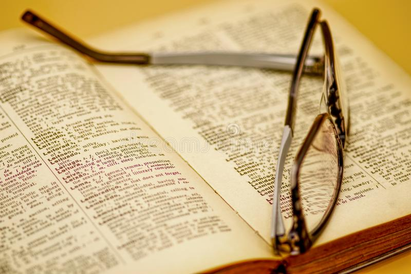Old book and reading glasses royalty free stock photos