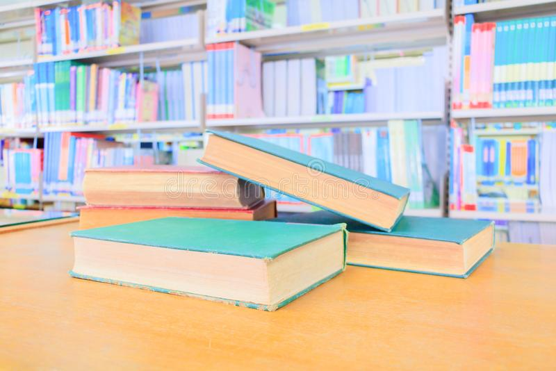 Old book red - green. and heap treatise in school library on wooden table. blurry bookshelves background. Education learning concept with copy space add text stock image