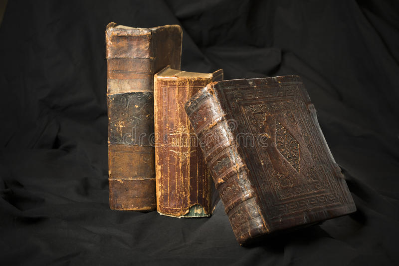 Old book spines on black background. Ancient library. Antique Ho. Ly Scripture books. Antique books collection. Wisdom knowledge in old books. Torn hard cover royalty free stock photos