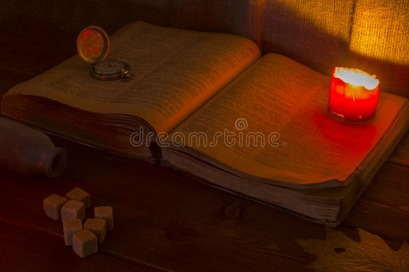 Old book on the table. The open Holy Bible is on the table. Vintage pocket watch. A burning candle over the Bible illuminates its royalty free stock images