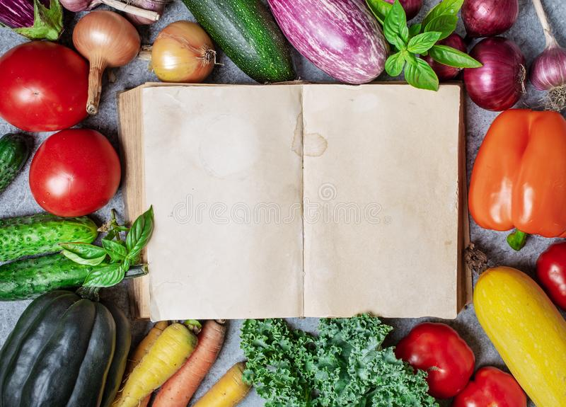Old book and vegetables. Open book with blank sheets of paper and vegetables around, top view royalty free stock images
