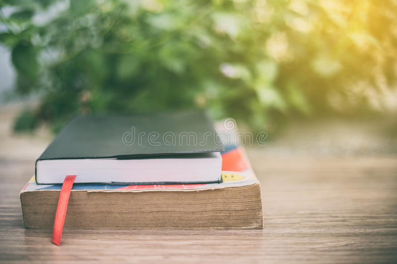 Old book on wooden table at home garden with nature bokeh backg stock photos