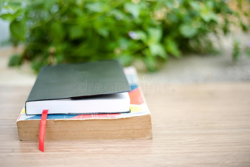 Old book on wooden table at home garden with nature bokeh backg royalty free stock photography