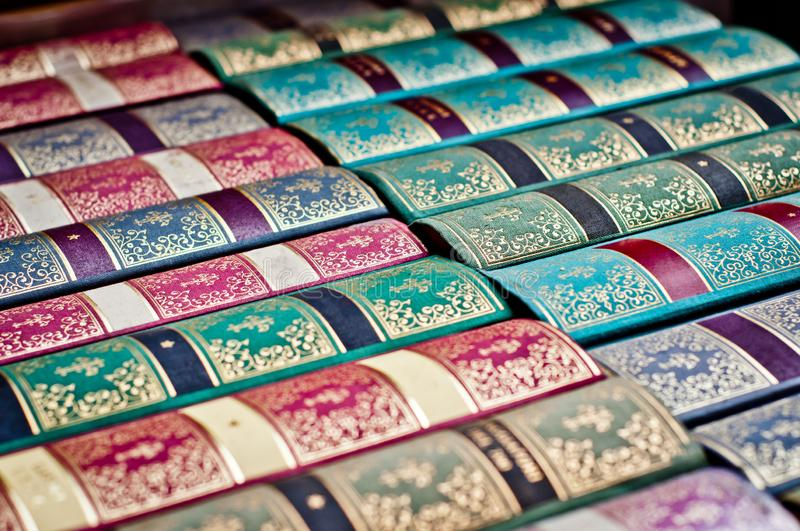 Old books background. Colorful ornamental book binding. Collection of old, aged books in a row. Leather hardcover manuscripts.  Colorful ornamental book binding royalty free stock photo