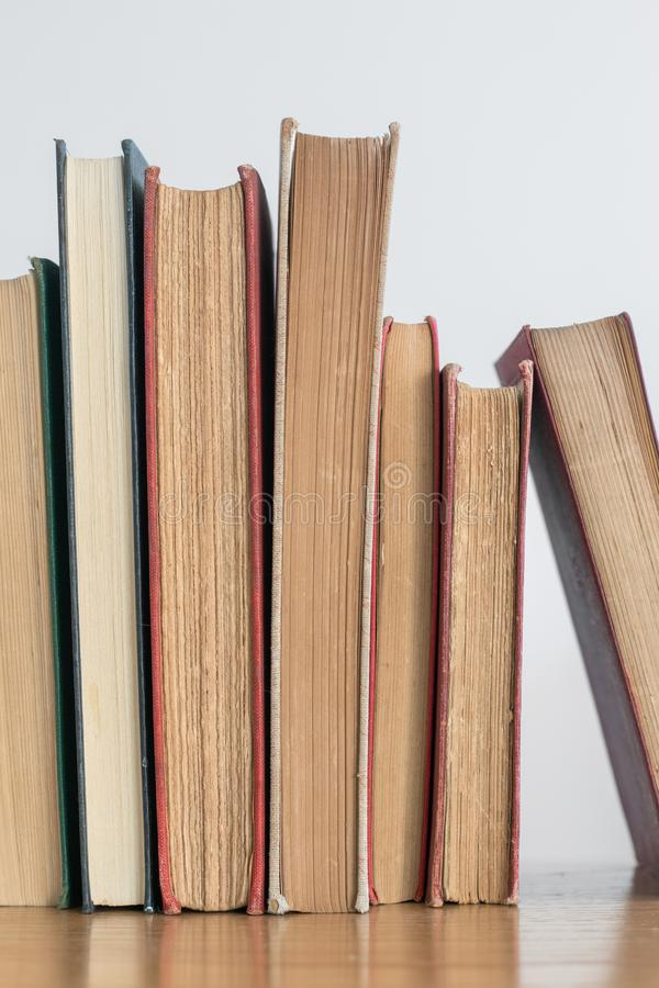 Row of old books on a wooden bookshelf. Row of old books standing upright on a wooden bookshelf, with a blank background stock photo