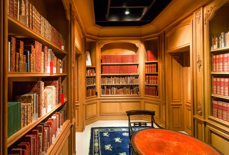 Old books on bookshelves with volumes and antique wooden table inside the library royalty free stock photography