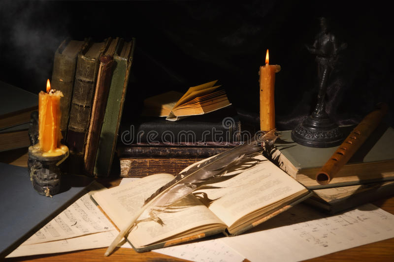 Old books and candles on wooden table stock images