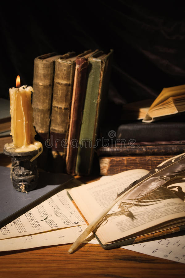 Old books and candles on wooden table stock photo