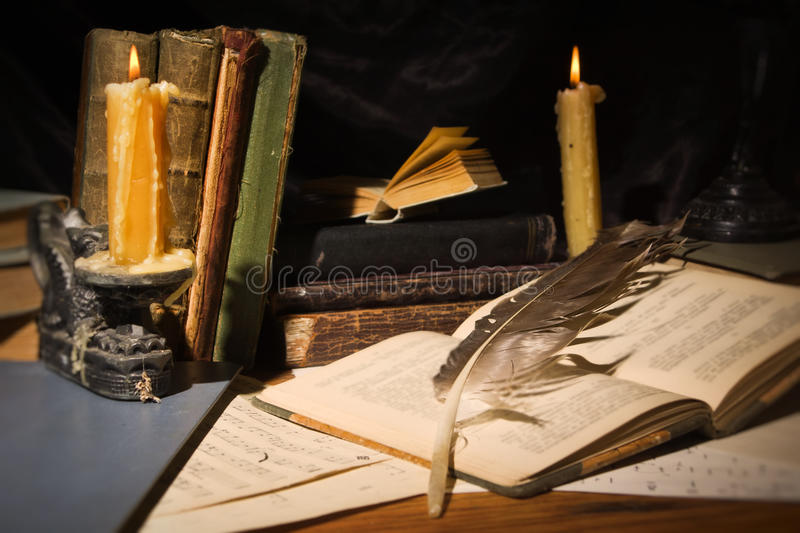 Old books and candles on wooden table stock image