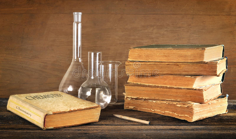 Old books and chemical glassware stock image