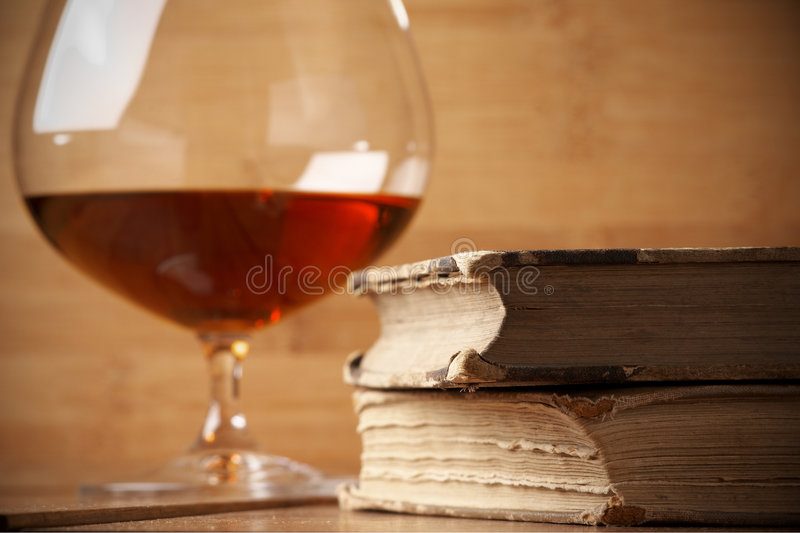 Old books and cognac royalty free stock photography