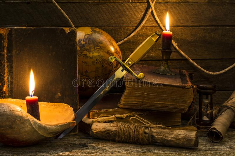 Old books and documents, a burning candle, globe and dirk stand on a wooden surface stock photo