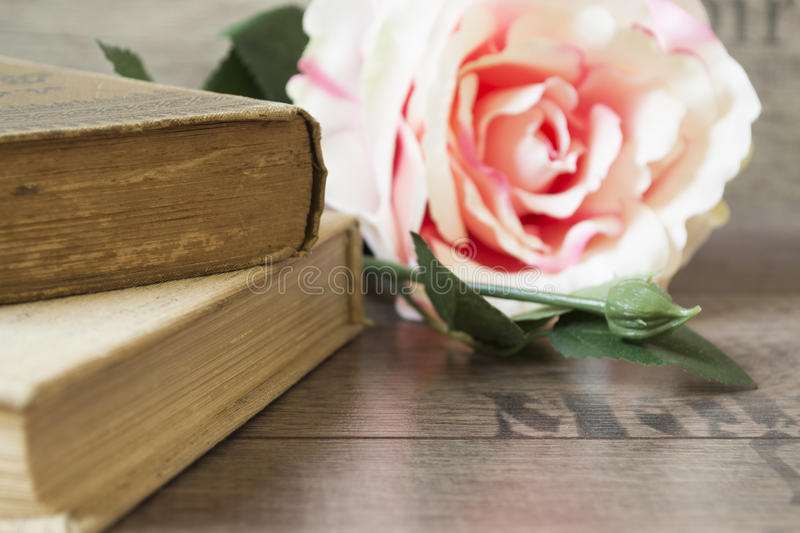 Old books and flower rose on a wooden background. Romantic floral frame background. Picture of a flowers lying on an antique book. Flowers on vintage wood stock photos
