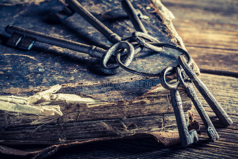 Old books and keys. Closeup of old books and keys on old wooden table royalty free stock images
