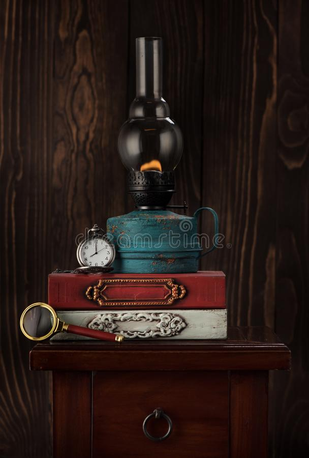 Old books, oil lamp and vintage watch on a chain. Retro still life stock photography