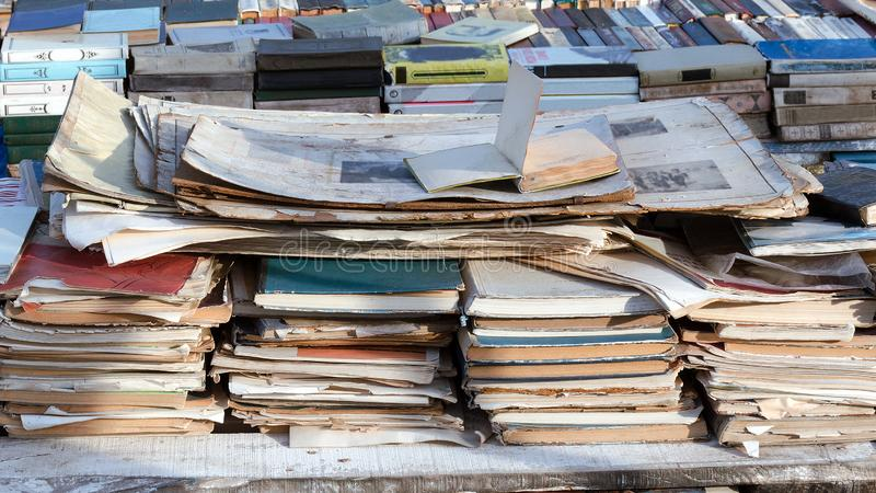 Old books and papers are stacked on the counter, selling vintage books royalty free stock photos