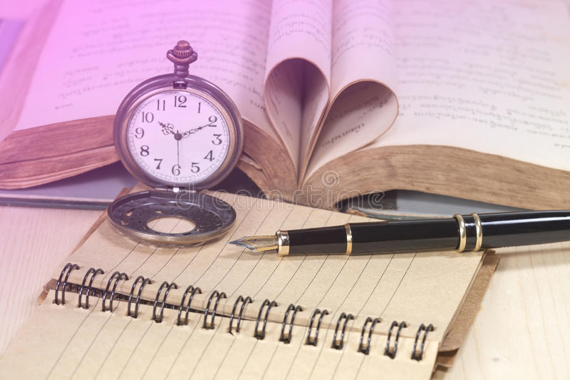 Old books, pocket clock, paper and fountain pen royalty free stock images