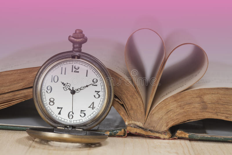 Old books and pocket watches on desk stock images
