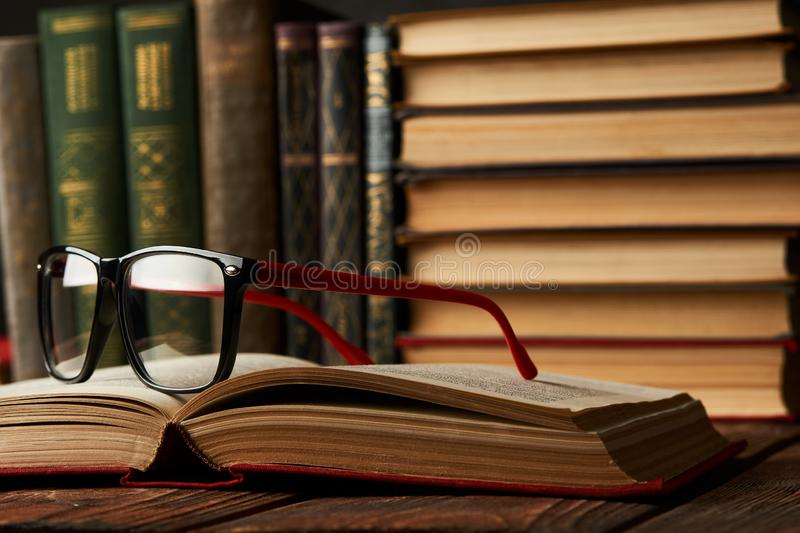 Old books and reading glasses on desk in library room royalty free stock images