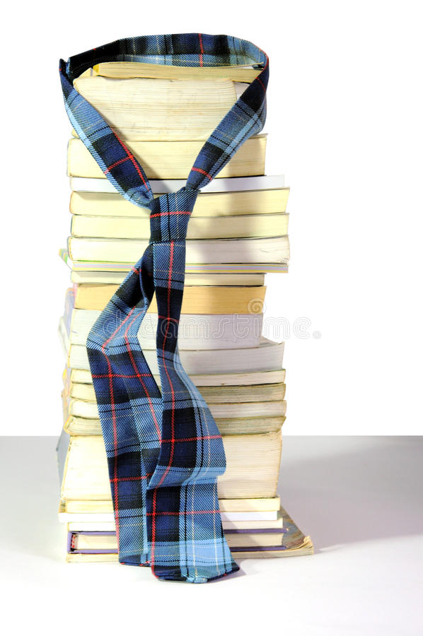 Old books and a tie on white background. Old book stack and a student's tie on white background stock photography