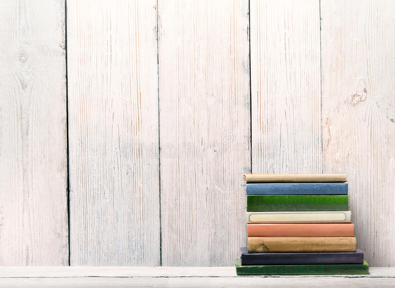 Old Books on Wood Shelf, Spine Cover over White Wooden Wall royalty free stock photos