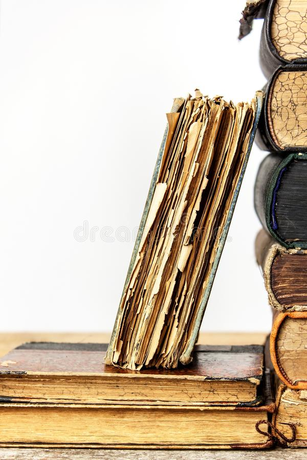 Old books on a wooden shelf on a white background. Study of old books. Damaged books. Old Library stock photos