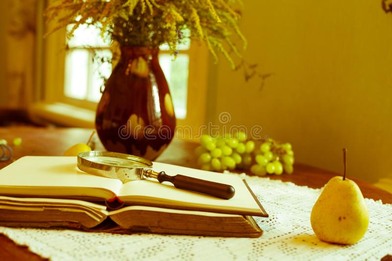 Old books on a wooden table and glass magnifier. Cute composition with old books in shabby grey cover and bouquet of flowers in a cup on wooden background stock photography