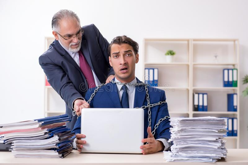 Old boss and young male employee in the office. The old boss and young male employee in the office stock images