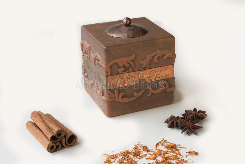 Old box with cinnamon , saffron, anise on white background stock image