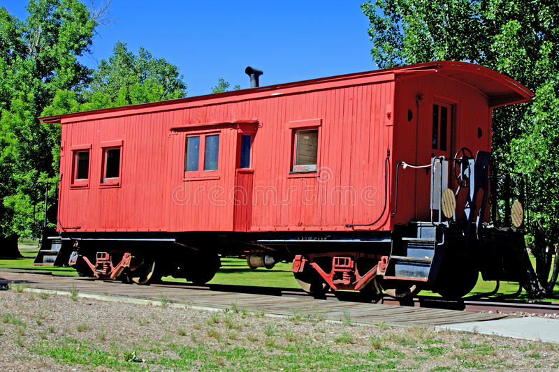 Old boxcar. On tracks with trees and blue sky stock photos