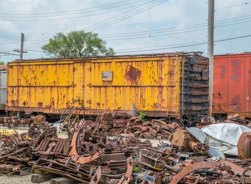 Old boxcar abandoned in train yard. Old boxcar and railroad junk left for scrap rusting in the rail yard royalty free stock photography