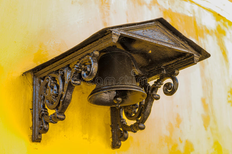 Old brass bell with ornate on yellow plaster wall. Old brass bell with ornate cover mounted on yellow plaster wall royalty free stock images