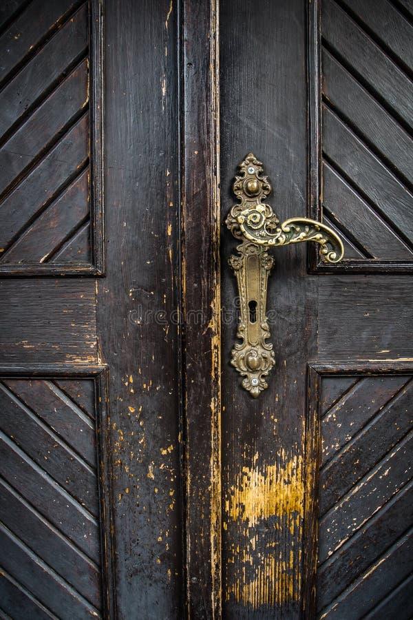 Old brass door handle. Antique brass door handle on old, partially damaged door royalty free stock photography