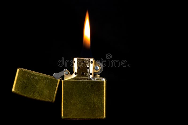 Old Brass Lighter and Flame on a Black Background stock images
